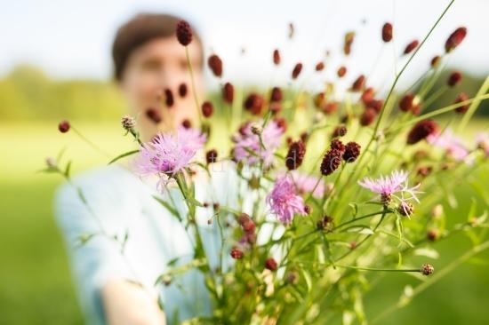 Frau hällt Blumen in die Kamera