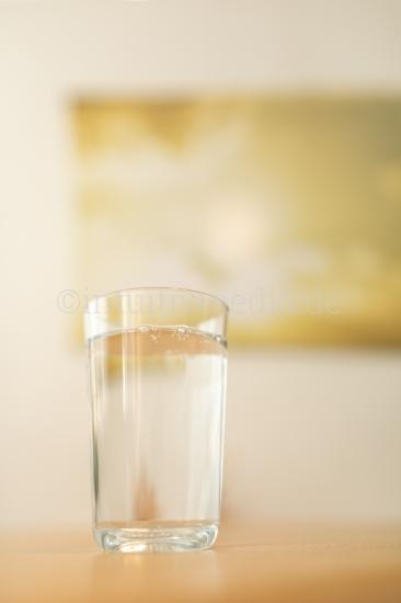 Volles Glass Wasser vor Gelb