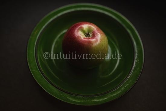 Roter Bio Apfel im grünen Teller