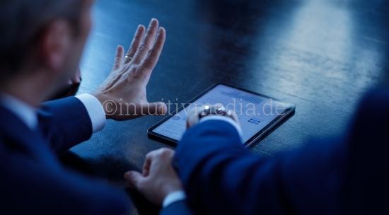 Geschäftsmann zeigt Kollegen eine Präsentation auf Tablett