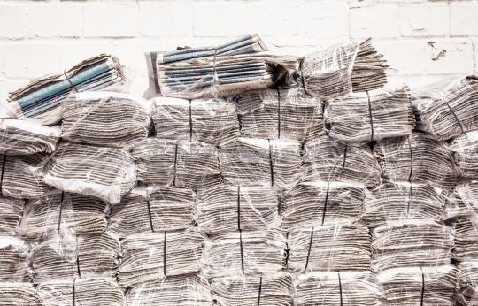 Stapel Zeitungen vor Wand