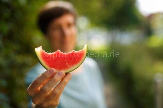 Frau hält Stück Wassermelone mit Bokeh