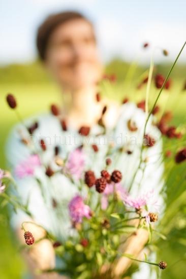 Frau lacht und zeigt Blumenstrauß