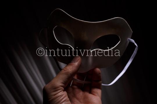 Hand hält Maske