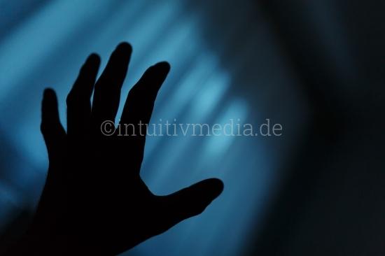 Dunkle Hand vor Fenster