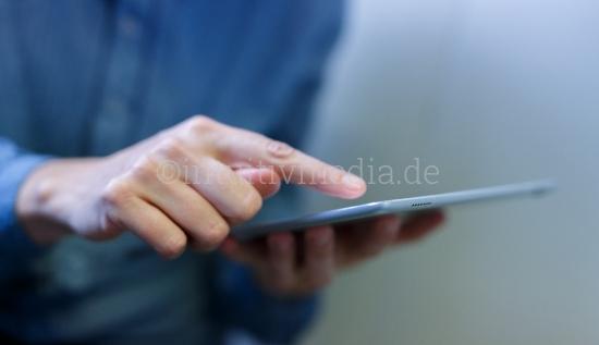 Frau zeigt auf Bildschirm von Tablet