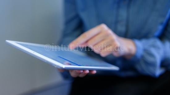 Frau zeigt auf Ipad Tablet