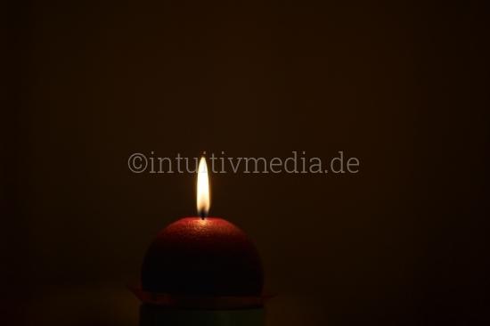 Rote Kerze im Dunkel