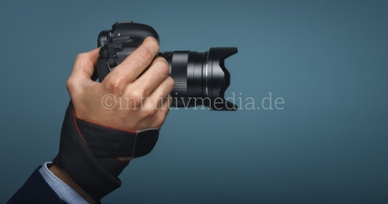 Hand mit DSLR Kamera