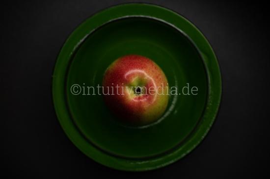 Roter Apfel im grünen Teller