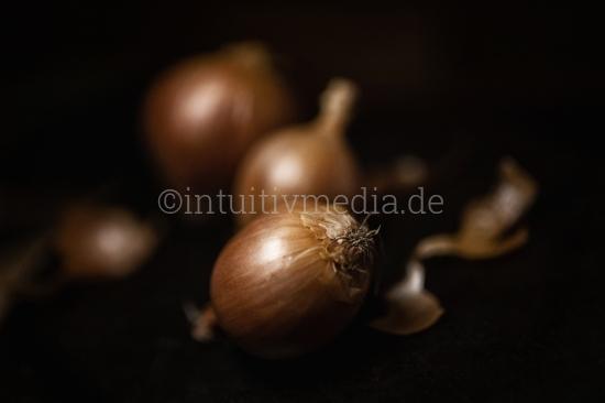 3 Zwiebeln vor dunklem Hintergrund