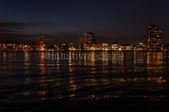 Hochhäuser nachts am Fluss