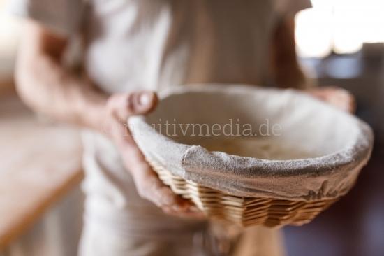 Bäcker mit Brotkorb in der Backstube